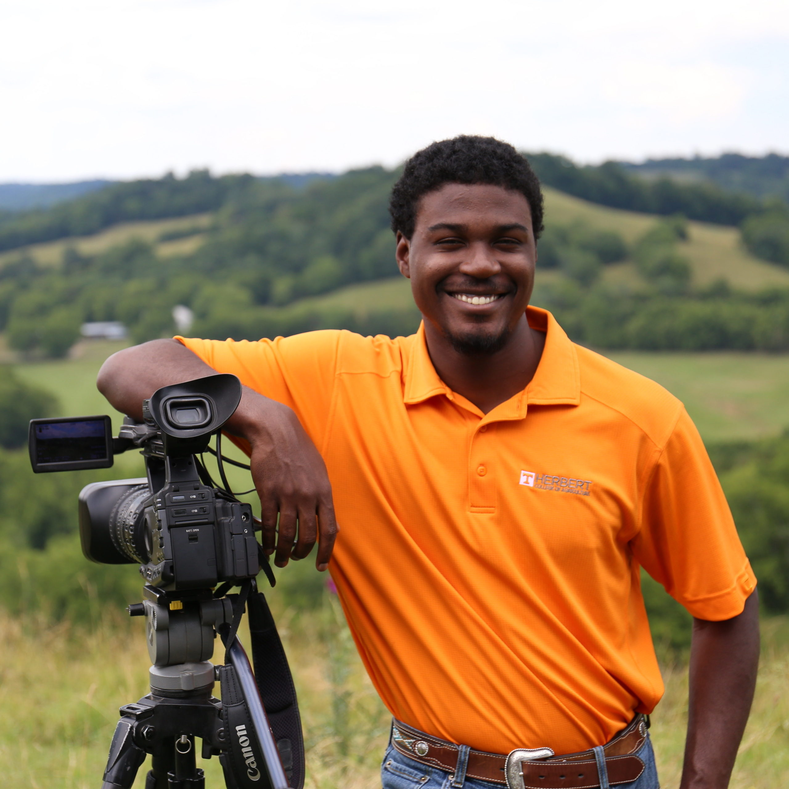 African American male student smiles and leans on a camera mounted on a tripod with the Tennessee hills in the background